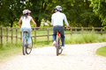 Indian couple on cycle ride in countryside cycling away from camera into distance Royalty Free Stock Photos