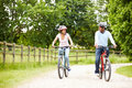 Indian couple on cycle ride in countryside wearing helmets smiling at each other Stock Photography