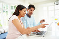 Indian couple making online purchase at home sitting down pointing to laptop screen Stock Photo