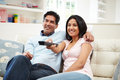 Indian couple sitting on sofa watching tv together pointing remote control Royalty Free Stock Photos