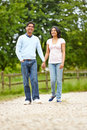 Indian couple walking in countryside holding hands smiling Stock Image