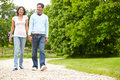 Indian couple walking in countryside holding hands smiling Royalty Free Stock Photo