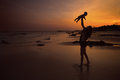 Indian family enjoying in the beach silhouette of an during sunset Royalty Free Stock Image
