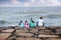 Indian family near the ocean puducherry india january sitting on stones in puducherry also known as pondicherry on january Stock Photography