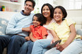 Indian family sitting on sofa watching tv together looking away from camera smiling Royalty Free Stock Photos