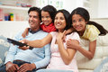 Indian family sitting on sofa watching tv together smiling whilst pointing remote control Royalty Free Stock Photo