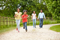 Indian family walking in countryside towards camera smiling Royalty Free Stock Photo