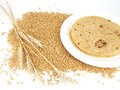 Indian flat bread chapati also known as in a ceramic plate on a spread of wheat grains with wheat sheaf Stock Photos