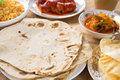 Indian food chapatti roti or chapati curry chicken biryani rice salad masala milk tea and papadom on dining table Royalty Free Stock Photography