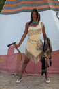Indian girl aggressive with an axe and shield in hand against the background of the teepee Royalty Free Stock Photos