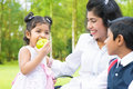 Indian girl eating apple happy family asian an green at outdoor with mother and sibling Royalty Free Stock Photos