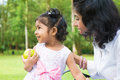 Indian girl holding an green apple outdoor happy family asian at with mother Stock Image