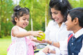 Indian girl sharing apple with family happy asian an green at outdoor mother and sibling Royalty Free Stock Photography