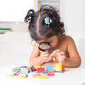 Indian girl zoom into toys through a magnifying glass little living lifestyle at home Stock Images
