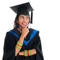 Indian graduate student thinking happy in graduation gown and cap and smiling portrait of beautiful asian female model standing Stock Images