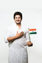 Indian handsome boy or man in white ethnic wear holding indian national flag and showing patriotism, standing isolated over white Royalty Free Stock Photo