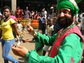 Indian man in traditional custume playing musical instrument.