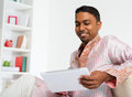 Indian man using digital tablet at home and pc young people pc Stock Image