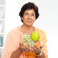 Indian mature woman healthy lifestyle old people eating portrait of a s holding fresh fruits at home indoor senior people living Stock Photo