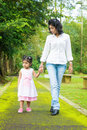 Indian mother and daughter walking outdoor family on garden path holding hands at park Stock Photo