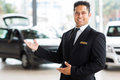 Indian salesman presenting handsome new car to clients Royalty Free Stock Photo