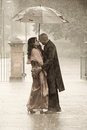 Indian smartly dressed couple holding an umbrella in the rain. Royalty Free Stock Photo