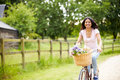 Indian woman on cycle ride in countryside with flowers basket Stock Photo