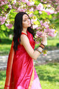Indian woman in the park beautiful asian on a warm spring day with blossom flowers around her Royalty Free Stock Images
