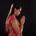Indian woman prayer portrait of beautiful young in traditional sari dress isolated on black background Stock Photo