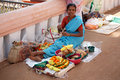 Indian woman sitting on the floor on the market near the hinduism temple and selling the goods for offering to the lord Royalty Free Stock Photo