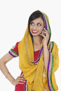 Indian woman in traditional wear answering phone call over white background Stock Photography
