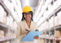 Indian woman in warehouse smiling doing stock tick with safety helmet smiling happy writing report portrait of beautiful asian Royalty Free Stock Image