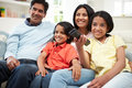 Indische familiezitting op sofa watching tv samen Stock Afbeelding