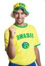 Indivíduo atrativo com jérsei brasileiro e chapéu que riem da câmera Fotos de Stock