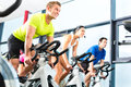 Indoor bycicle cycling in gym young people group of women and men doing sport spinning the for fitness Royalty Free Stock Images
