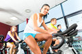 Indoor bycicle cycling in gym young people group of women and men doing sport spinning the for fitness Royalty Free Stock Image