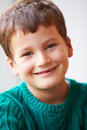 Indoor portrait of boy wearing jumper smiling at camera Royalty Free Stock Photo