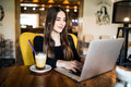 Indoor portrait of a young girl she works as a freelancer in a cafe drinking a delicious hot Cup of coffee from text send mail loa Royalty Free Stock Photo