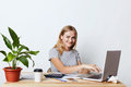 Indoor shot of attractive businesswoman with happy expression, keyboarding at laptop computer, being busy with making financial re Royalty Free Stock Photo