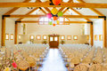 Indoor wedding ceremony venue location for a with rows of white chairs Stock Photos