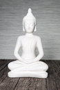 Indoor white seated statue buddha sitting lotus position clasped hands meditating praying weathered timber boards Stock Photography