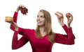 Indulge yourself woman with four arms holding fruit and cakes in each hand Stock Photo