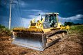 Industrial backhoe, bulldozer moving earh and sand in sandpit Royalty Free Stock Photo