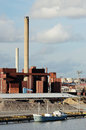 Industrial building and chimney and boat against the gray sky Royalty Free Stock Photos