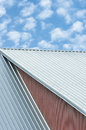 Industrial building roof sheets, grey steel rooftop pattern, bright summer clouds cloudscape, blue sky, rifled roofing panels Royalty Free Stock Photo