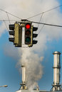 Industrial chimney and red traffic lights of an company a light symbolic photo for environmental protection ozone Royalty Free Stock Images