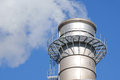 Industrial chimney releasing gasses in to a blue clear sky Stock Photography