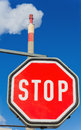 Industrial chimney and stop sign Royalty Free Stock Image