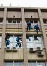 Industrial climbers engaged in washing the Windows of a high-rise building Royalty Free Stock Photo