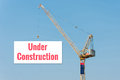 """Industrial construction crane holding a billboard with """"under x text on blue sky background elegant design for Royalty Free Stock Photography"""